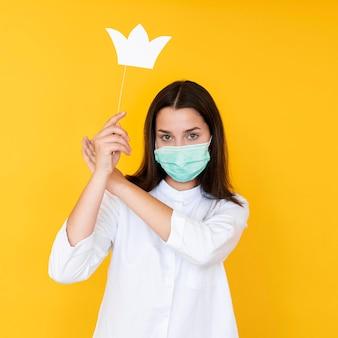 Vista frontal de uma garota usando uma coroa com máscara facial