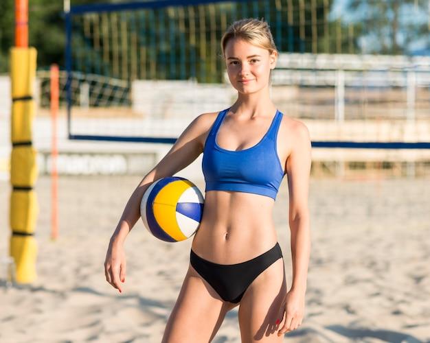 Vista frontal de uma jogadora de vôlei segurando uma bola na praia enquanto posa