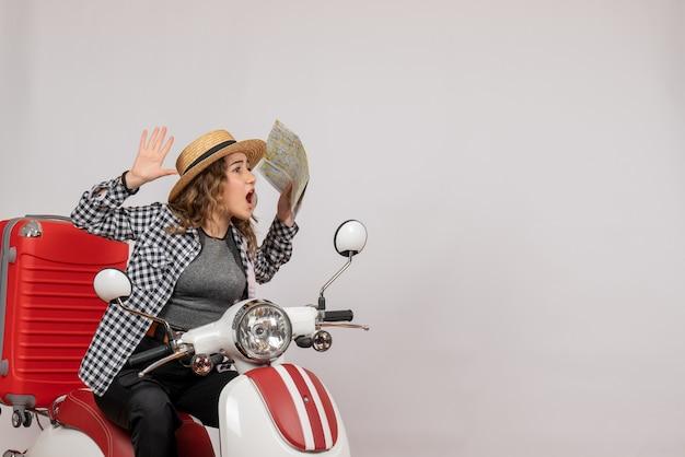 Vista frontal de uma jovem agitada em uma motocicleta segurando o mapa na parede cinza