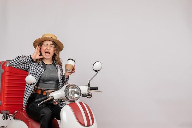 Vista frontal de uma jovem agitada em uma motocicleta segurando um café na parede cinza