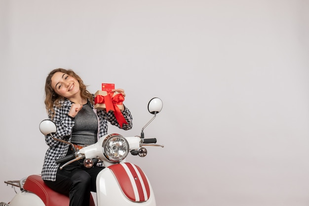 Vista frontal de uma jovem alegre em uma motocicleta segurando um presente na parede cinza