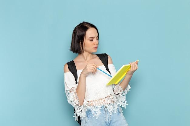 Vista frontal de uma jovem aluna em jeans azul e bolsa preta escrevendo notas