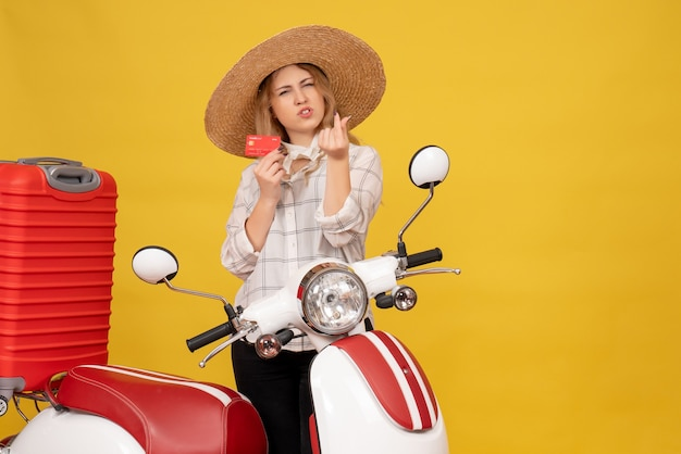 Vista frontal de uma jovem ambiciosa com chapéu, recolhendo a bagagem, sentada na motocicleta e segurando o cartão do banco, fazendo gesto de dinheiro