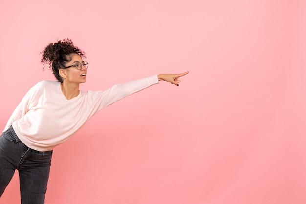 Vista frontal de uma jovem apontando na parede rosa