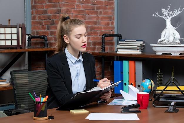 Vista frontal de uma jovem assistente confiante sentada em sua mesa e escrevendo seu documento no escritório