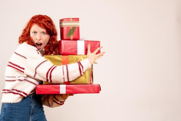 Vista frontal de uma jovem carregando presentes de natal na parede branca