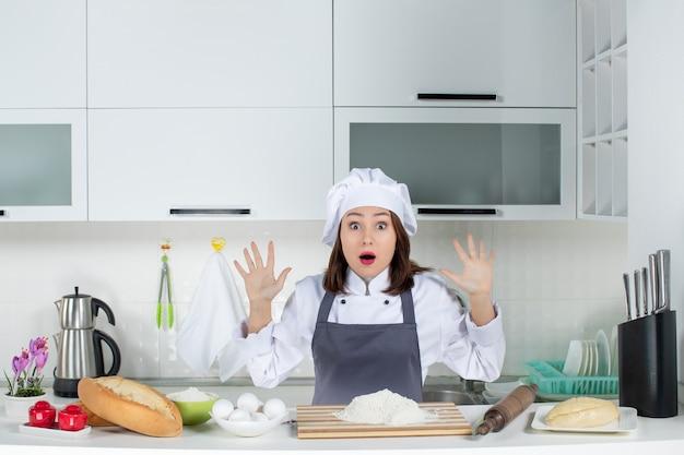 Vista frontal de uma jovem chef assustada de uniforme, em pé atrás da mesa, com uma tábua de cortar alimentos na cozinha branca
