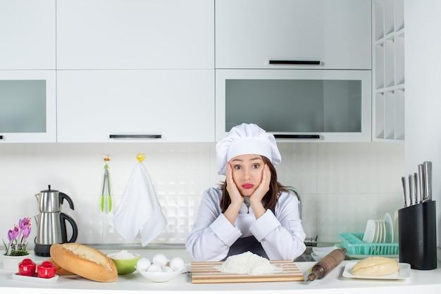 Vista frontal de uma jovem chef feminina confusa e insatisfeita, de uniforme, em pé atrás da mesa, com uma tábua de cortar alimentos na cozinha branca