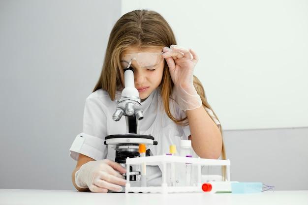 Vista frontal de uma jovem cientista curiosa usando um microscópio