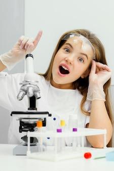 Vista frontal de uma jovem cientista usando microscópio e tendo uma ideia