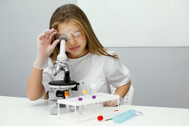 Vista frontal de uma jovem cientista usando microscópio