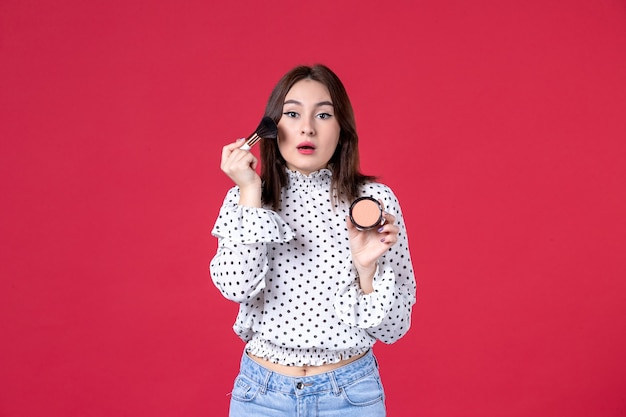 Vista frontal de uma jovem com borla e pó fazendo maquiagem na parede vermelha