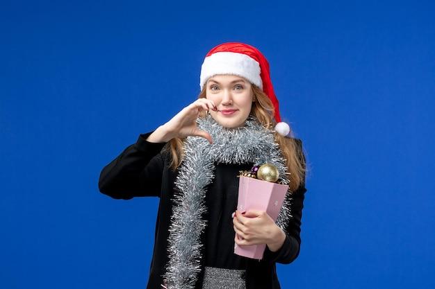 Vista frontal de uma jovem com brinquedos para árvores de ano novo na parede azul
