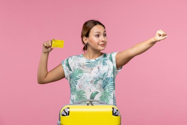 Vista frontal de uma jovem com cartão amarelo e bolsa na parede rosa
