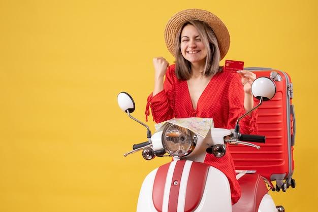 Vista frontal de uma jovem com chapéu-panamá segurando o cartão do banco na motocicleta