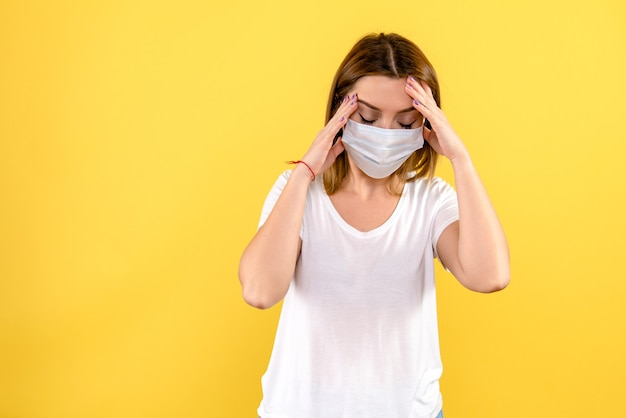 Vista frontal de uma jovem com dor de cabeça na parede amarela