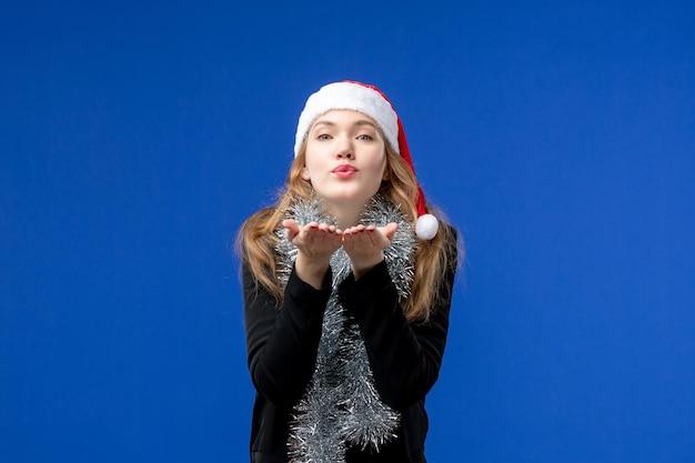 Vista frontal de uma jovem com guirlandas de ano novo na parede azul
