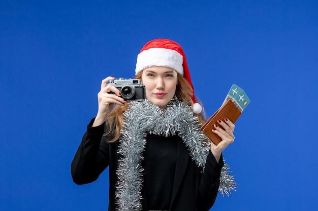 Vista frontal de uma jovem com ingressos e câmera na parede azul