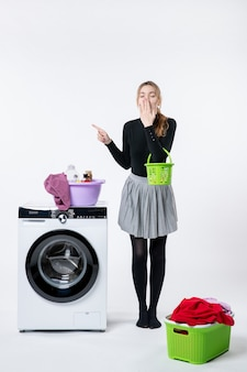 Vista frontal de uma jovem com máquina de lavar e roupas sujas na parede branca