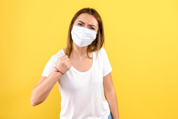 Vista frontal de uma jovem com máscara estéril na parede amarela