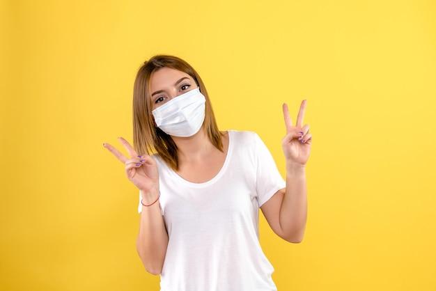Vista frontal de uma jovem com máscara na parede amarela