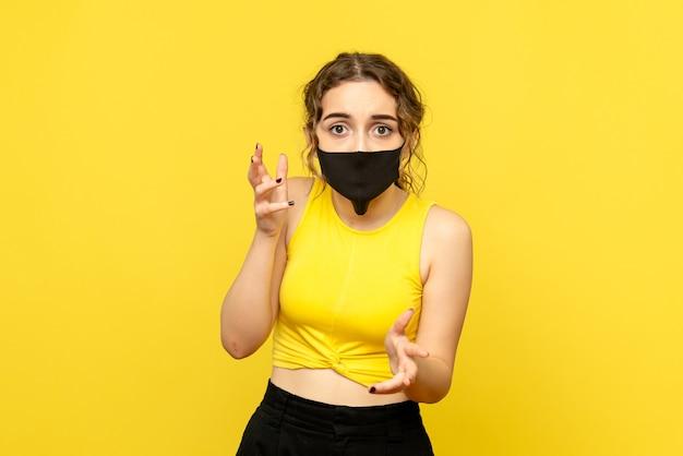Vista frontal de uma jovem com máscara preta na parede amarela