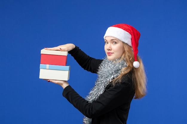 Vista frontal de uma jovem com os presentes de ano novo na parede azul