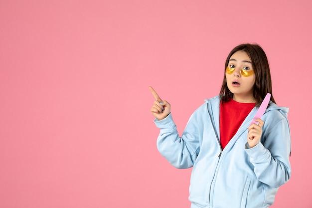 Vista frontal de uma jovem com tapa-olhos e lixa de unha na parede rosa