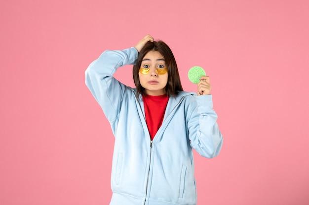 Vista frontal de uma jovem com tapa-olhos e uma pequena esponja na parede rosa
