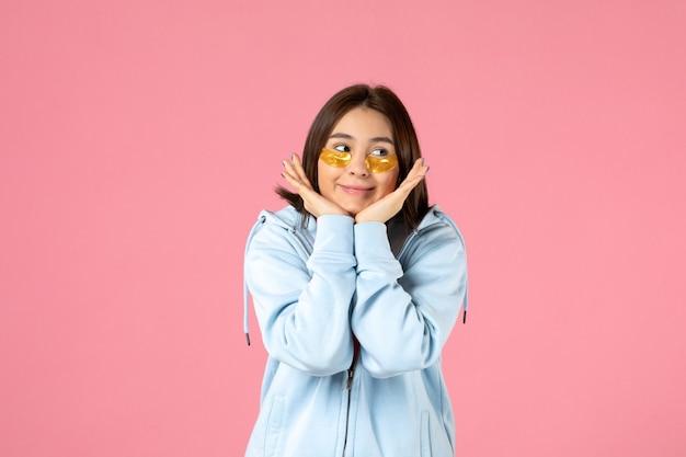 Vista frontal de uma jovem com tapa-olhos na parede rosa