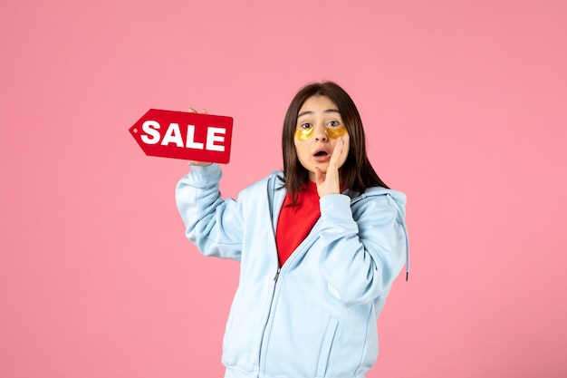 Vista frontal de uma jovem com tapa-olhos segurando um banner de venda na parede rosa