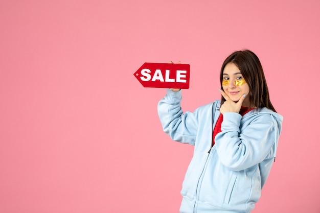 Vista frontal de uma jovem com tapa-olhos segurando um banner vermelho de venda na parede rosa
