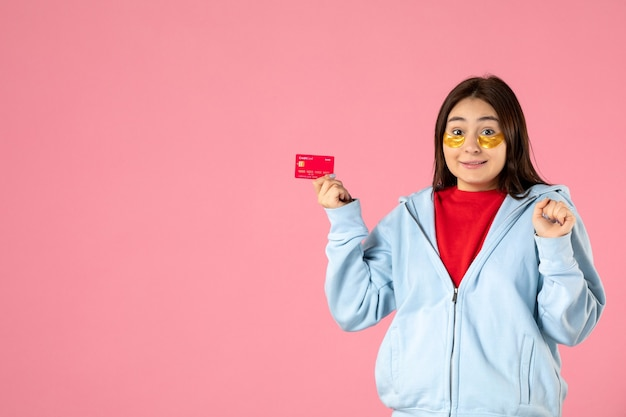 Vista frontal de uma jovem com tapa-olhos segurando um cartão do banco na parede rosa