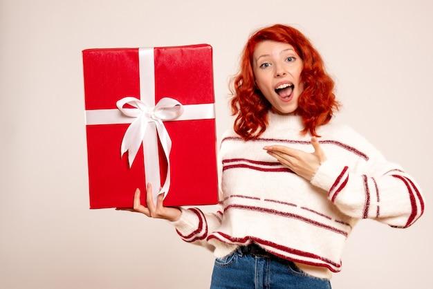 Vista frontal de uma jovem com um grande presente na parede branca