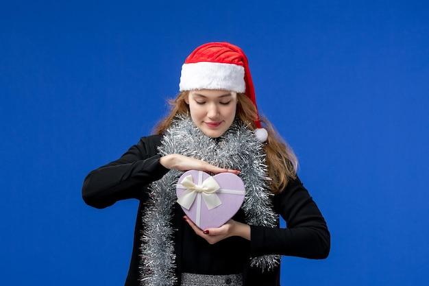 Vista frontal de uma jovem com um presente de ano novo na parede azul
