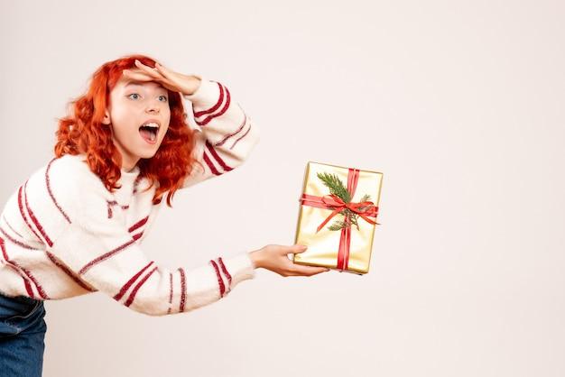 Vista frontal de uma jovem com um presente de natal na parede branca
