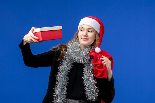 Vista frontal de uma jovem com uma bolsa de presente e um presente na parede azul
