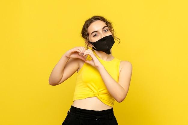 Vista frontal de uma jovem com uma máscara enviando amor na parede amarela
