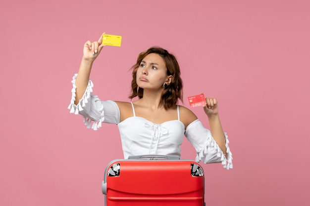 Vista frontal de uma jovem com uma sacola de férias segurando cartões bancários na parede rosa claro