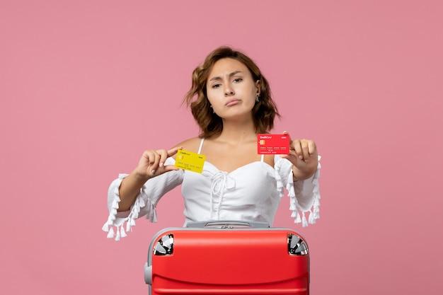 Vista frontal de uma jovem com uma sacola de férias segurando cartões bancários na parede rosa