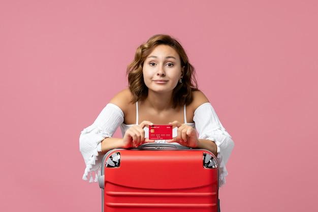Vista frontal de uma jovem com uma sacola de férias segurando um cartão do banco na parede rosa