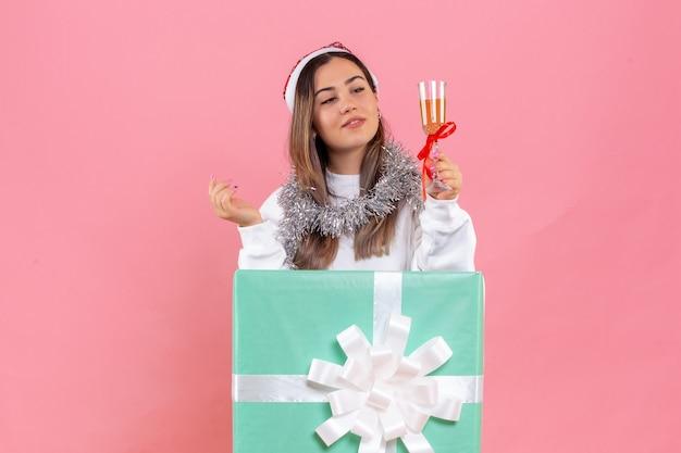 Vista frontal de uma jovem comemorando o natal com uma bebida na parede rosa