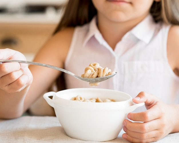 Vista frontal de uma jovem comendo cereais no café da manhã