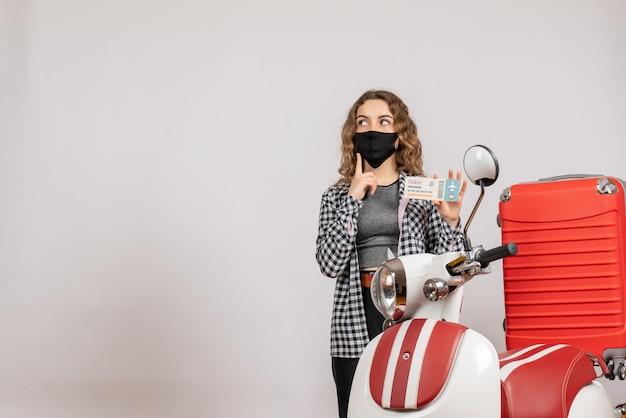 Vista frontal de uma jovem confusa com uma máscara em pé perto de um ciclomotor com uma mala