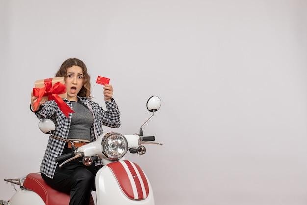 Vista frontal de uma jovem confusa em um ciclomotor segurando um cartão e um presente na parede cinza