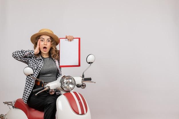 Vista frontal de uma jovem confusa em uma motocicleta segurando uma prancheta na parede cinza