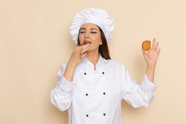 Vista frontal de uma jovem cozinheira em um terno branco, comendo biscoitos na parede branca