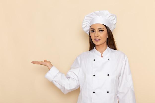 Vista frontal de uma jovem cozinheira em um terno branco, posando com a mão levantada na parede branca