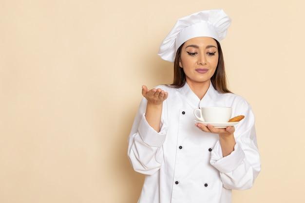 Vista frontal de uma jovem cozinheira em um terno branco segurando café na parede branca