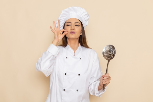 Vista frontal de uma jovem cozinheira em um terno branco segurando uma colher de prata grande na parede branca